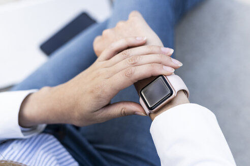 Businesswoman checking smartwatch, close up - GIOF05788