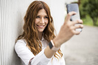 Young businesswoman commuting in the city, taking selfies - GIOF05806