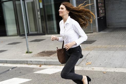 Businesswoman running in the street - GIOF05809