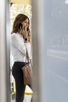 Businesswoman waiting at bus station, using smartphone - GIOF05812
