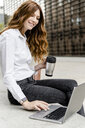 Young businesswoman sitting on bench in the city, working with laptop, drinking coffee - GIOF05824