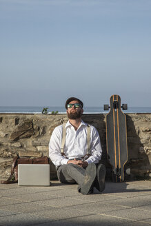 Man sitting between laptop and longboard on the ground relaxing - KBF00574