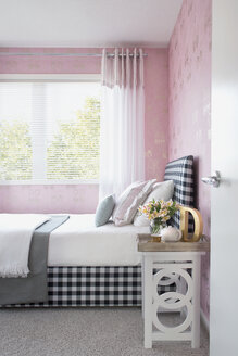Pastel pillows on bed with gingham headboard - HEROF27867