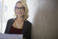 Portrait smiling blonde businesswoman with paperwork along wall - HEROF27879