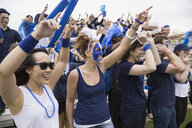 Enthusiastic crowd in blue cheering at sports event - HEROF27939