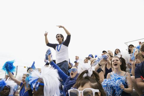 Enthusiastic man in blue standing cheering in bleachers - HEROF27942