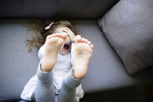 High angle view of happy girl hiding face while lying on sofa at home - CAVF62892