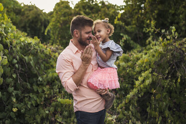 Father carrying cute daughter while standing against plants in park - CAVF62904