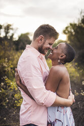 Side view of happy couple embracing while standing amidst plants against sky in park during sunset - CAVF62907