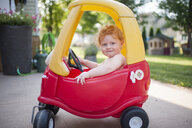 Portrait of cute shirtless baby boy sitting in toy car at backyard - CAVF62922