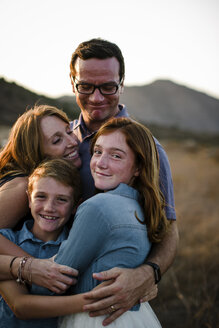 Portrait of smiling girl embracing family while standing together on field during sunset - CAVF62968