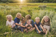 Cute friends sitting together on field by plants during sunset - CAVF62983