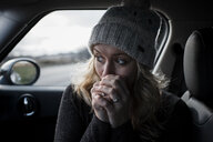 Close-up of woman with hands clasped looking away while sitting in car - CAVF63001