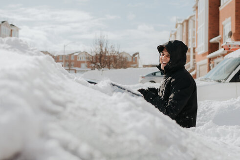 Man laughing beside snow-covered vehicle, Toronto, Canada - ISF20960