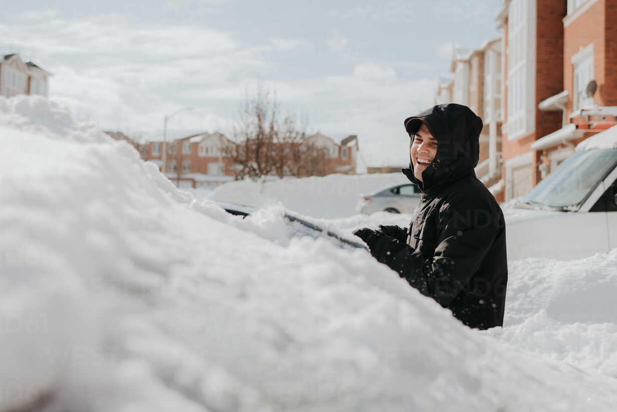 Man laughing beside snow-covered vehicle, Toronto, Canada - ISF20960 - Sara Monika/Westend61