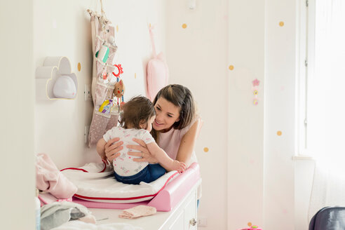 Mother talking to baby girl on changing table - ISF20975