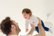 Father playing with baby girl at home - ISF20984
