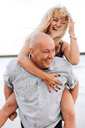 Couple playing piggyback ride on beach - ISF21002