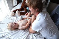 Father playing with baby boy on bed - ISF21008