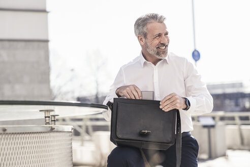 Smiling mature businessman with briefcase outdoors - UUF16607