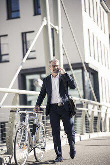 Happy mature businessman with bicycle talking on cell phone in the city - UUF16616