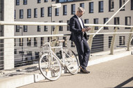 Mature businessman with bicycle using cell phone in the city - UUF16619