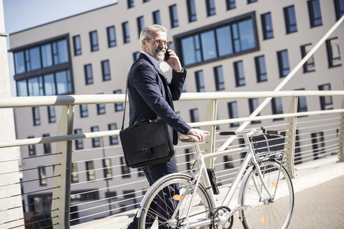Smiling mature businessman with bicycle talking on cell phone in the city - UUF16622