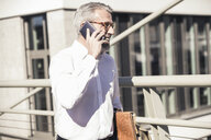 Happy mature businessman talking on cell phone in the city - UUF16625