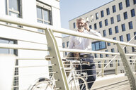 Smiling mature businessman with bicycle using cell phone in the city - UUF16631
