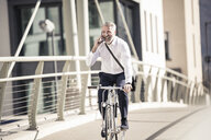 Happy mature businessman talking on cell phone and riding bicycle on a bridge in the city - UUF16634