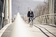 Smiling mature businessman with headphones riding bicycle on a bridge in the city - UUF16637