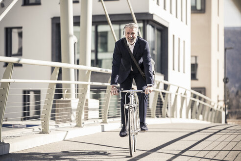 Smiling mature businessman with headphones riding bicycle on a bridge in the city - UUF16640