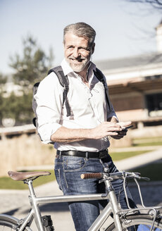 Portrait of smiling mature businessman with bicycle, cell phone and earphones - UUF16643