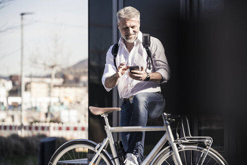 Smiling mature businessman with bicycle and earphones using cell phone - UUF16646