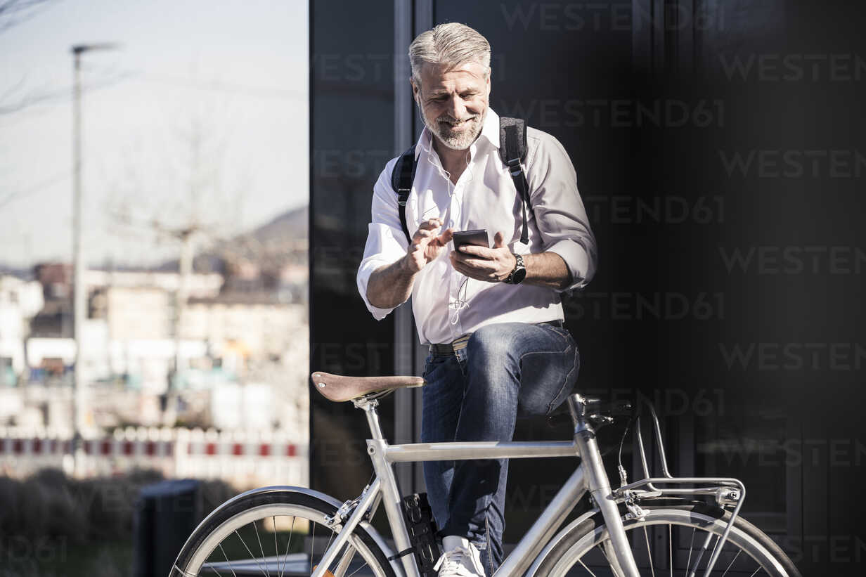 Smiling mature businessman with bicycle and earphones using cell phone - UUF16646 - Uwe Umstätter/Westend61