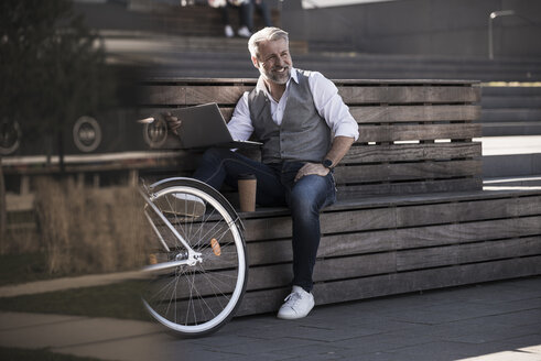 Smiling mature businessman with bicycle sitting on a bench using laptop - UUF16649