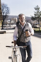 Smiling mature businessman with bicycle, takeaway coffee and headphones on the go in the city - UUF16655