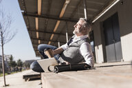 Mature businessman with laptop outdoors enjoying the sunshine - UUF16658