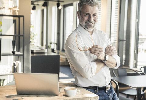 Portrait of confident mature businessman in office - UUF16682