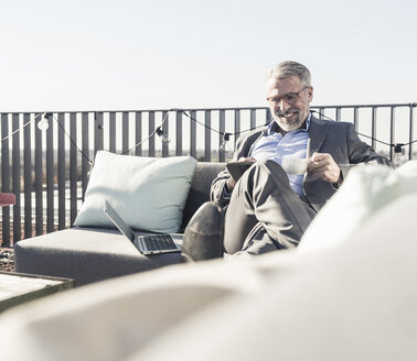 Smiling mature businessman using tablet on roof terrace - UUF16685