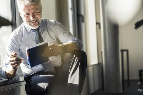 Smiling mature businessman sitting at the window with notebook - UUF16700