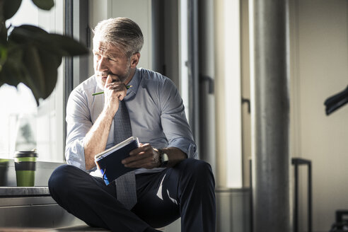 Mature businessman sitting at the window with notebook - UUF16703