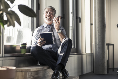 Happy mature businessman with notebook sitting at the window using cell phone - UUF16709