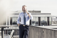 Smiling mature businessman on cell phone on roof terrace - UUF16712