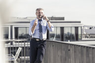 Happy mature businessman on cell phone on roof terrace - UUF16715
