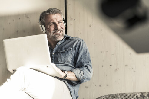 Casual mature businessman sitting down with laptop and headphones - UUF16724