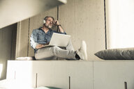 Casual mature businessman sitting down with laptop and headphones - UUF16727