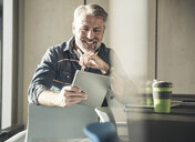 Smiling casual mature businessman sitting at desk using tablet - UUF16730