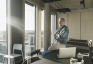 Smiling casual mature businessman looking out of window in office - UUF16742