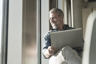 Smiling casual mature businessman with laptop looking out of window - UUF16745